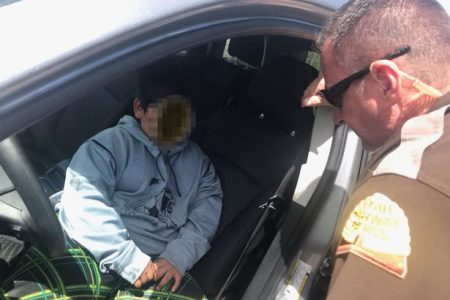 Menino dentro de carro e policial interrogando