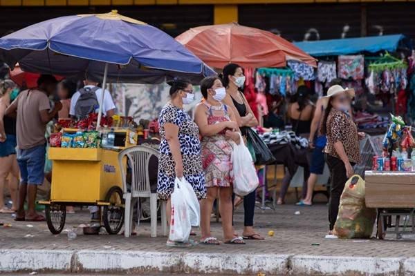 Pessoas caminham entre ambulantes no centro de Ceilândia
