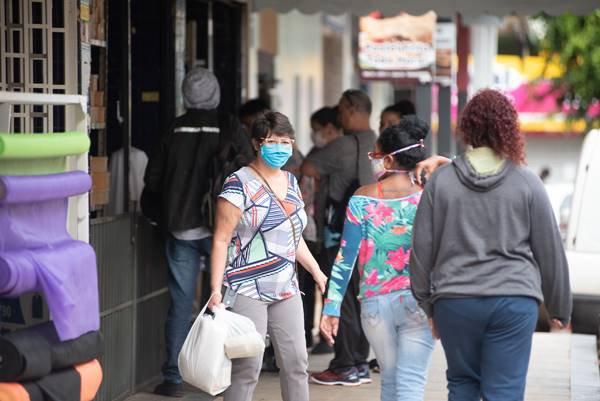 Mulher de mascara carrega sacola com produtos