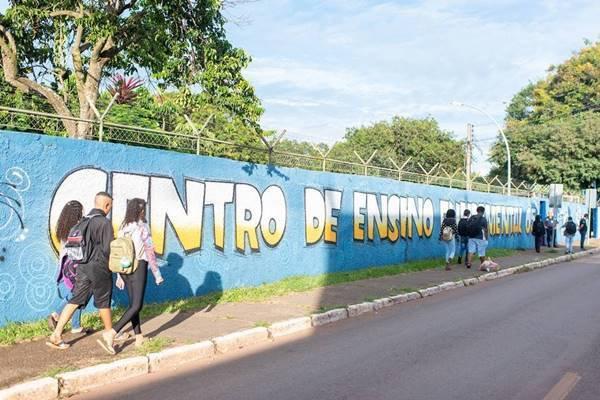 Estudantes caminham em frente de escola