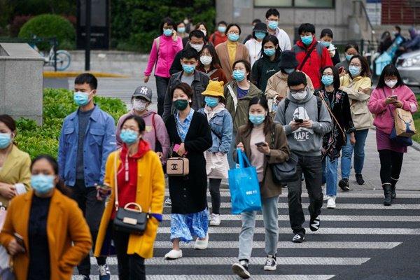 Na China, pessoas atravessam a rua usando máscara