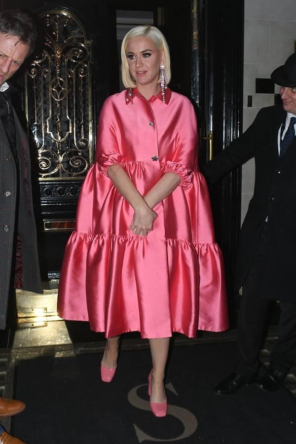 Katy Perry com vestindo rosa escondendo a gravidez com as maos