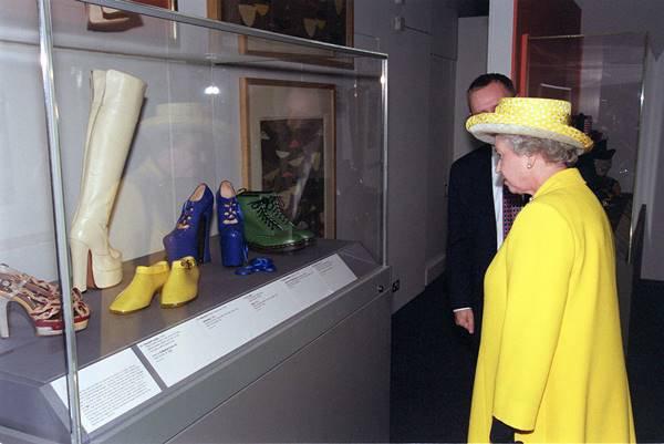 Rainha Elizabeth II no museu Victoria & Albert vendo o sapato Vivienne Westwood que derrubou Naomi Campbell em 1993