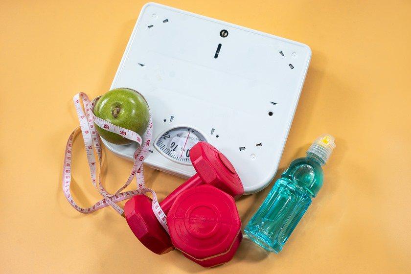 Balança, haltere, fruta, fita métrica e garrafa de água