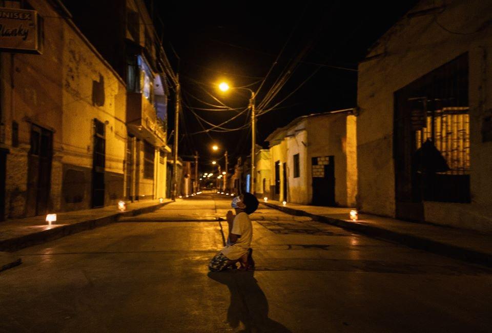 Menino ajoelhado à noite rezando no Peru