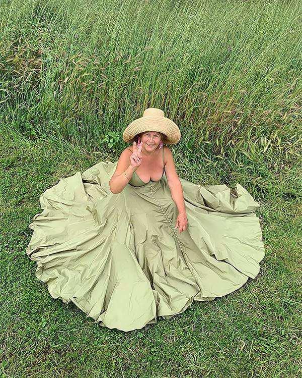 mulher com vestido longo sentada na grama