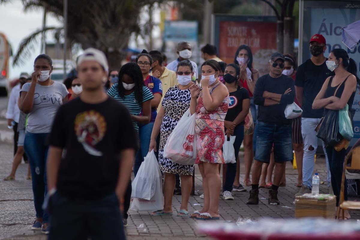 moradores do df usam máscaras e aguardam ônibus em parada