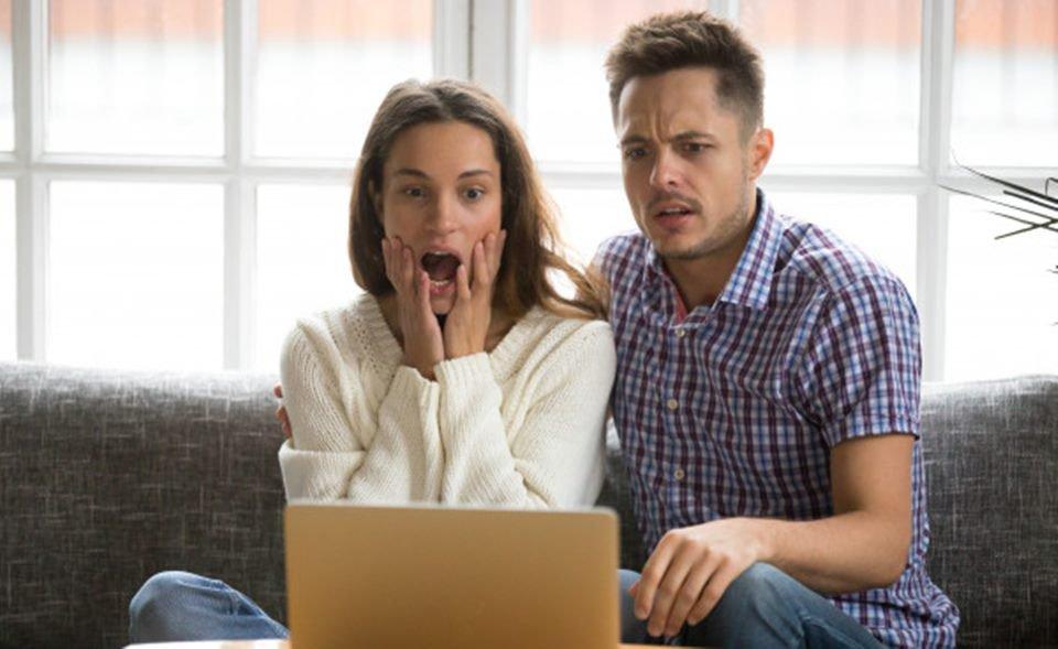 casal chocado em frente ao omputador