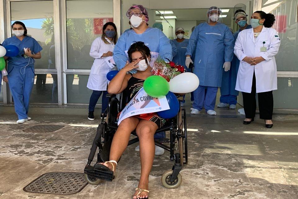 paciente da covid-19, em cadeira de rodas, chora na saída de hospital