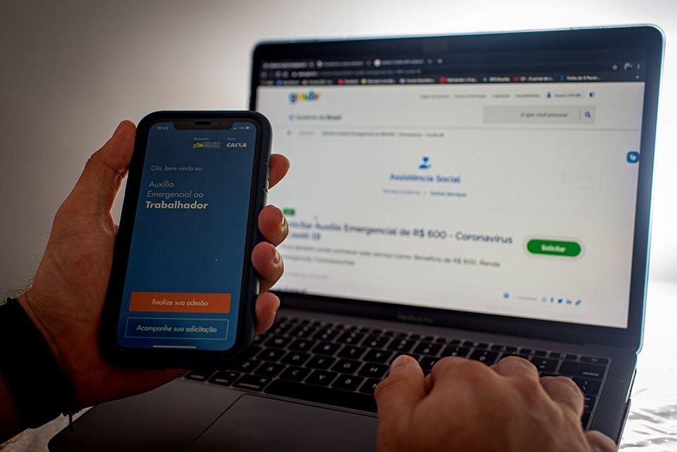 Aplicativo da caixa na mão do celular e computador ao fundo