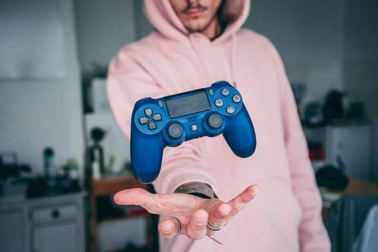 Pessoa jogando console do videogame pro alto
