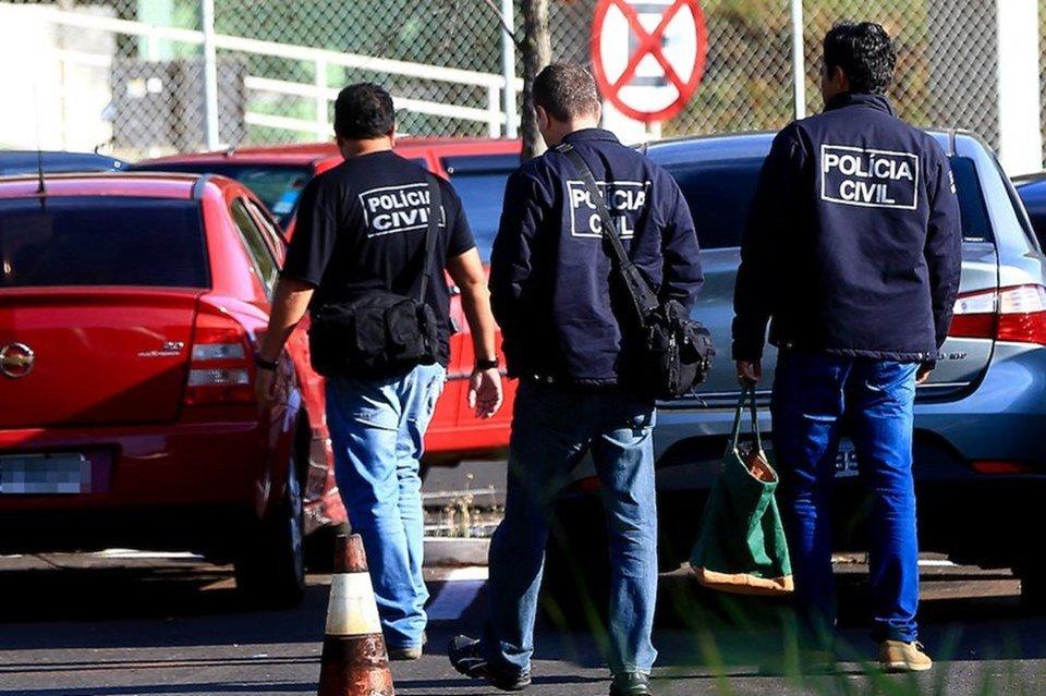 Três agentes da PCDF, de costas, caminhando