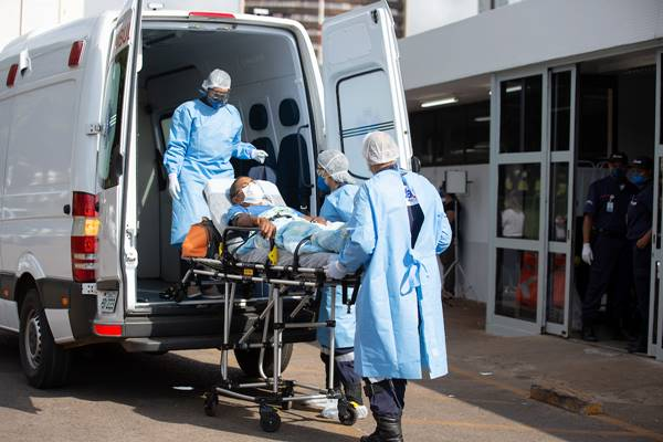 Equipe médica transporta paciente em maca
