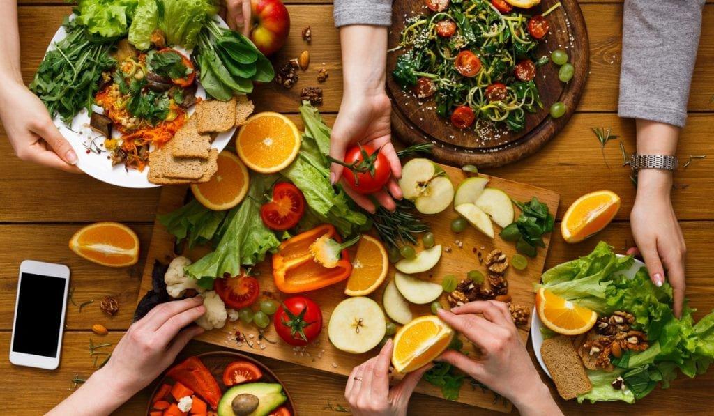 Mãos com frutas, verduras e legumes