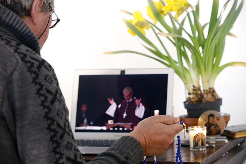 Homem acompanha missa on-line