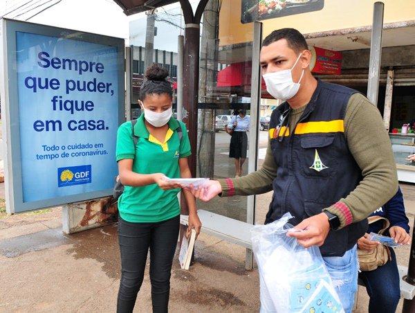 Servidor GDF distribuindo máscara a mulher