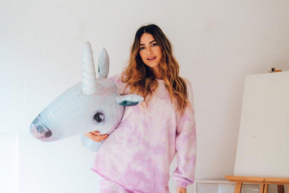 Thaila Ayala usando roupa tie-dye e segurando unicórnio de pelúcia