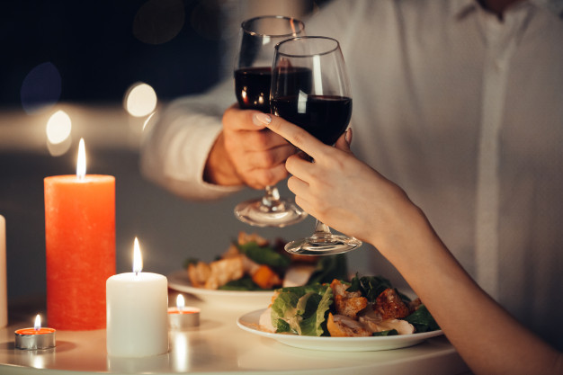 Casal brindando com vinho em jantar romântico