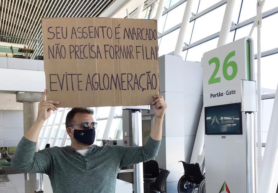 Homem com placa no aeroporto, pedindo fim das filas e aglomeração