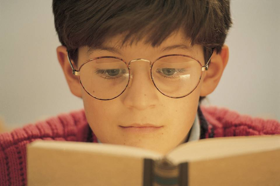 menino de óculos lendo livro
