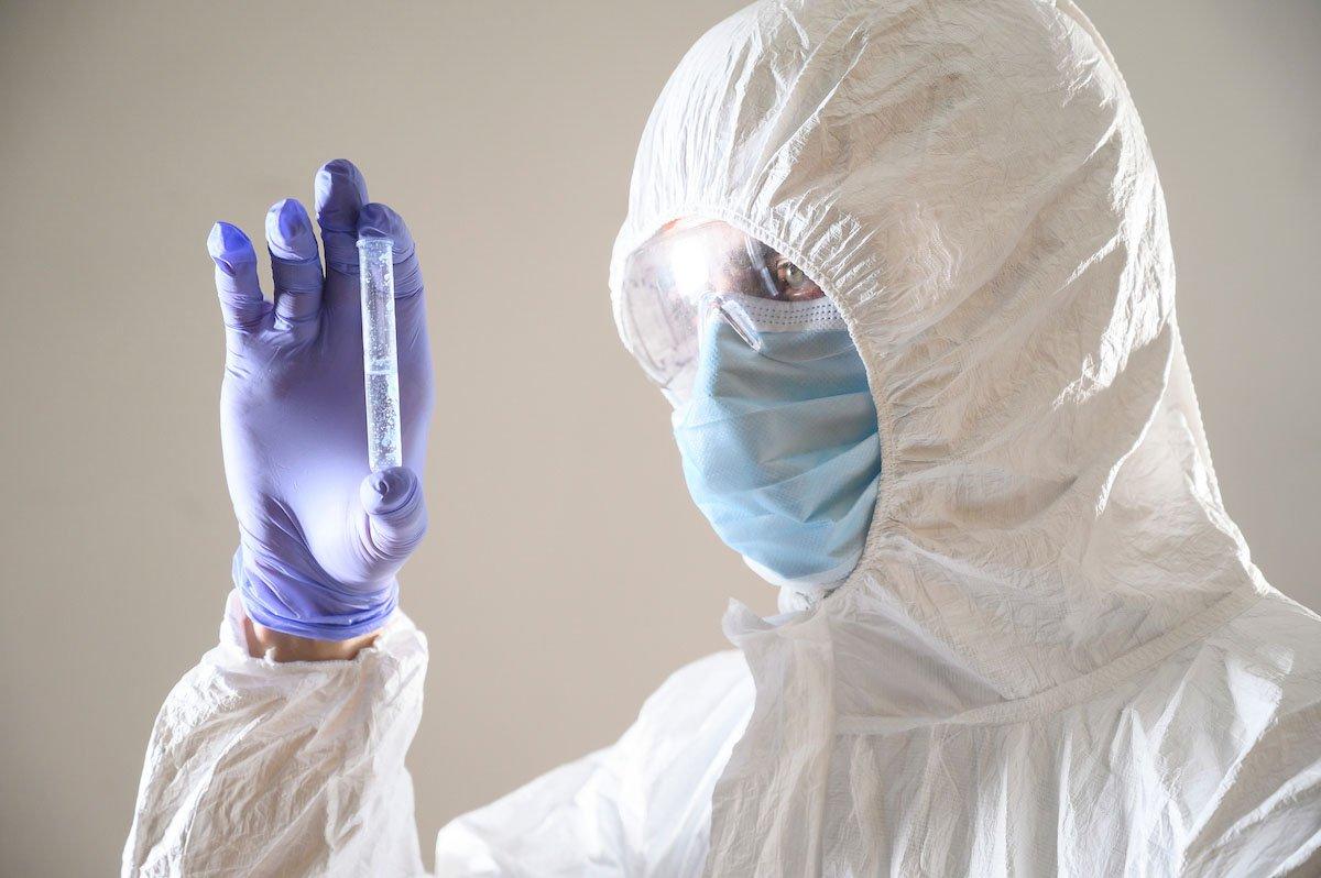 Cientista com mascara e EPI examina amostra de coronavirus