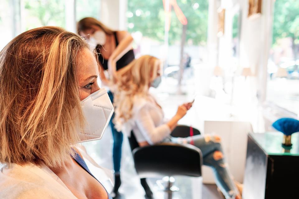 Clientes e profissionais de beleza de máscara no salão
