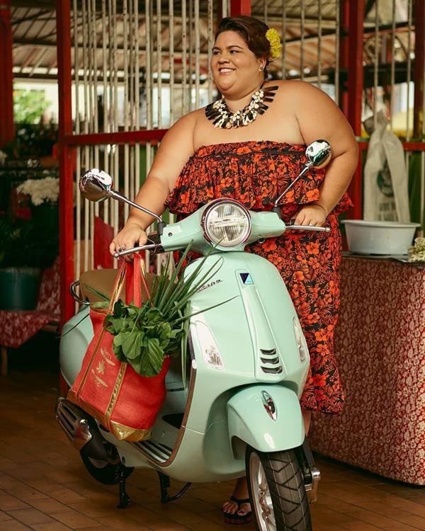 Mulher posando com uma Vespa
