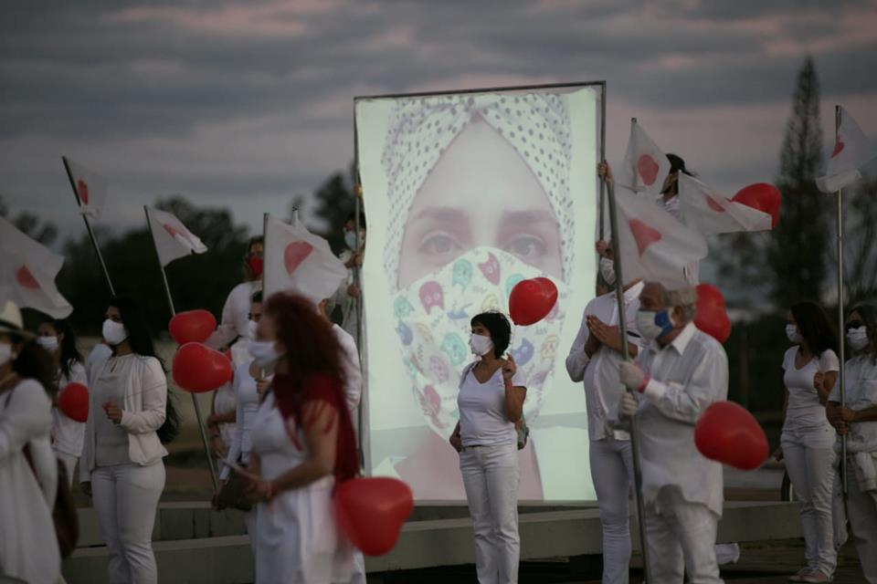 Pessoas de jaleco branco com balões vermelhos