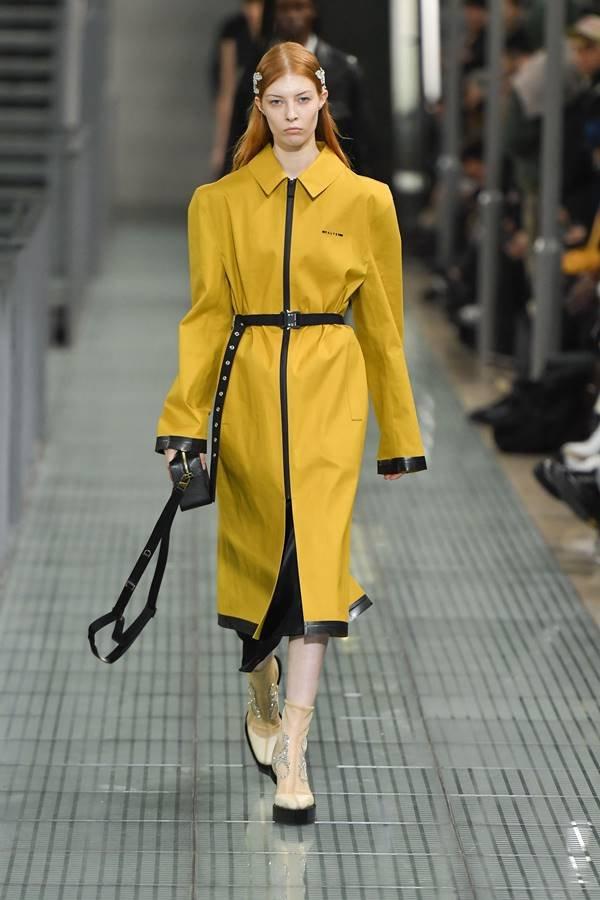 Modelo desfilando com casaco amarelo da marca 1017 ALYX 9SM