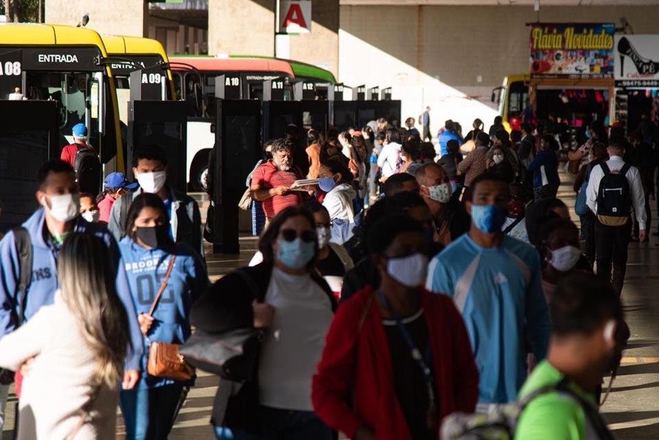 Pessoas de máscaras na Rodoviária