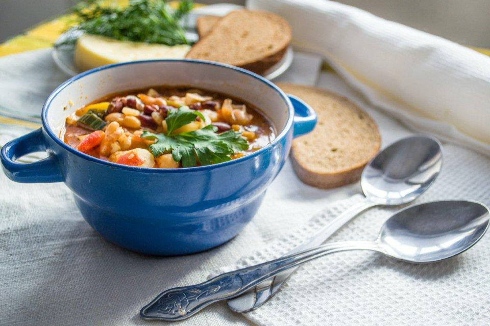 Sopa de legumes e feijão branco, bowl de sopa com colheres e torradas
