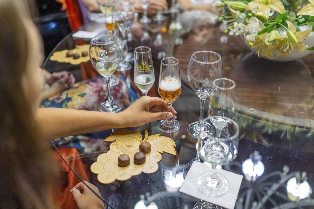 Taças, chocolates e espumantes em cima de uma mesa de vidro