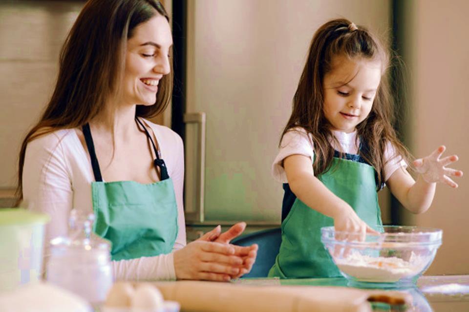 Criança cozinhando com a mãe