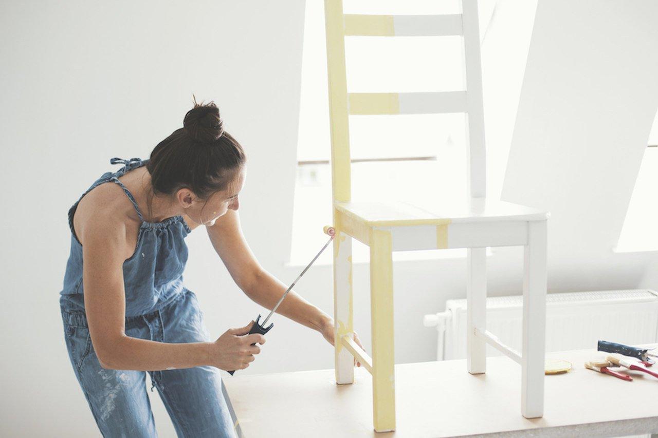 mulher pintando móvel de madeira