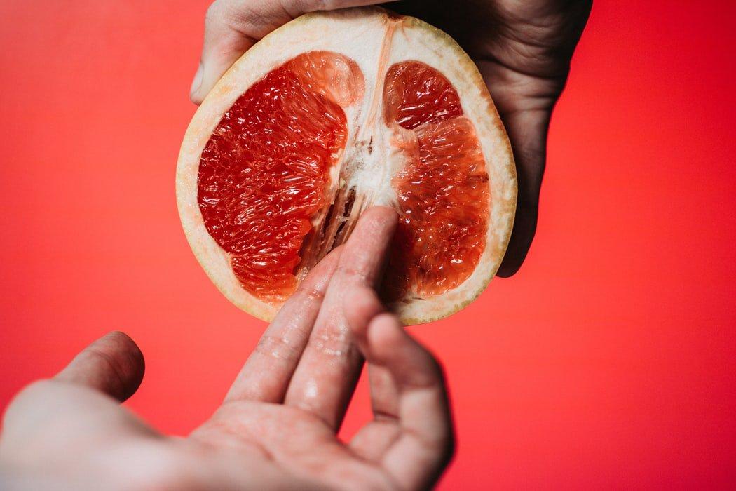 Mão segurando metade de uma laranja