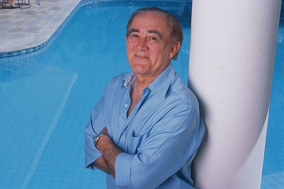Renato Aragão em frente a uma piscina, de braços cruzados