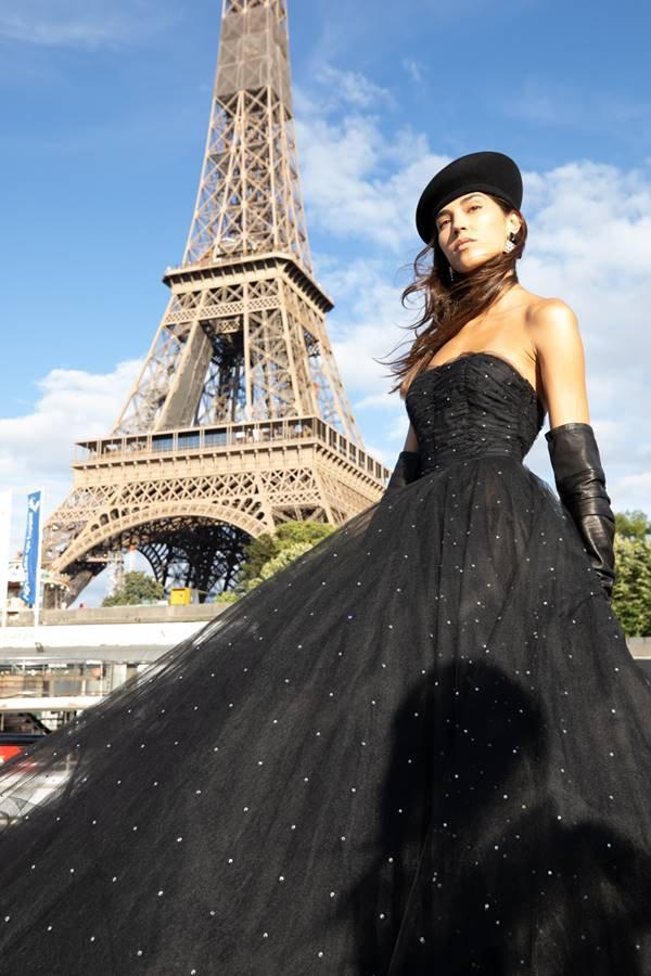 Modelo posando com peças da Balmain com a torre Eiffel ao fundo