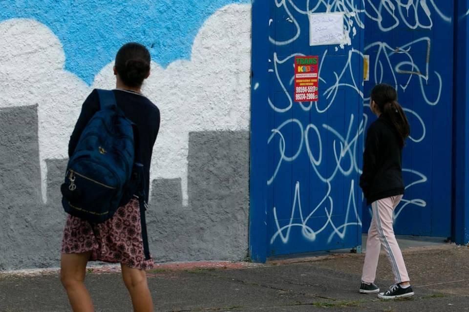 Aluno em frente de escola fechada