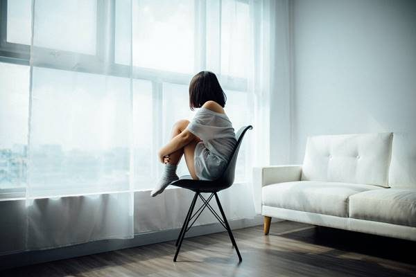 Garota sentada em uma cadeira olhando pela janela