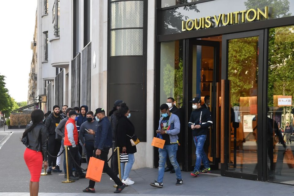 Pessoas fazendo fila em frente a loja da Louis Vuitton em Paris