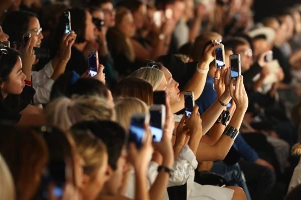 Pessoas com celulares em plateia de desfile de moda