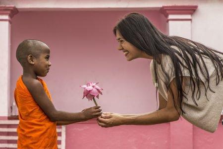 Menino entrega flor para mulher