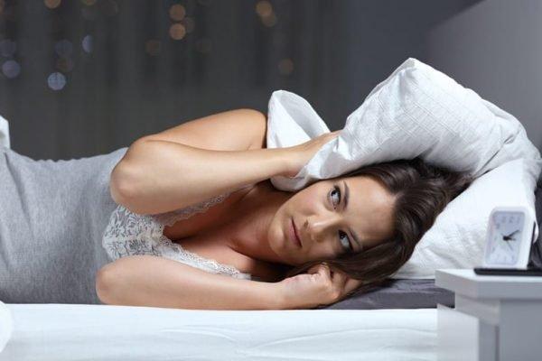 Mulher tentando dormir sem conseguir por causa do barulho