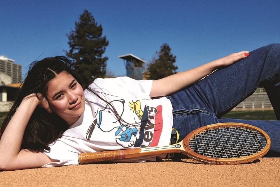 Modelo usa camiseta branca e calça jeans enquanto posa deita no chão com raquete de tênis