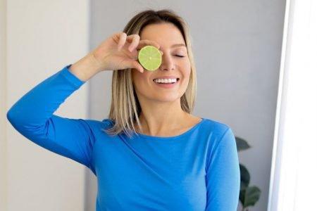 Samanta Piacini, fundadora da marca Lemon Basics, segurando uma rodela de limão em frente ao olho