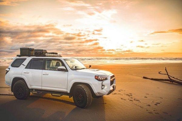 Carro estacionado em praia durante o por do sol, road trip