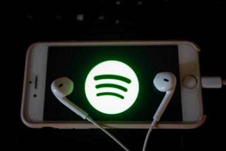 Celular com logomarca do Spotify e fones de ouvido