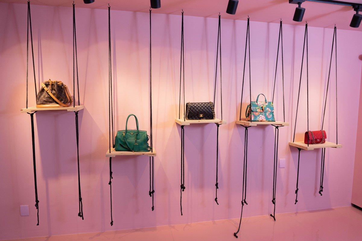 Showroom com bolsas de luxo em parede rosa