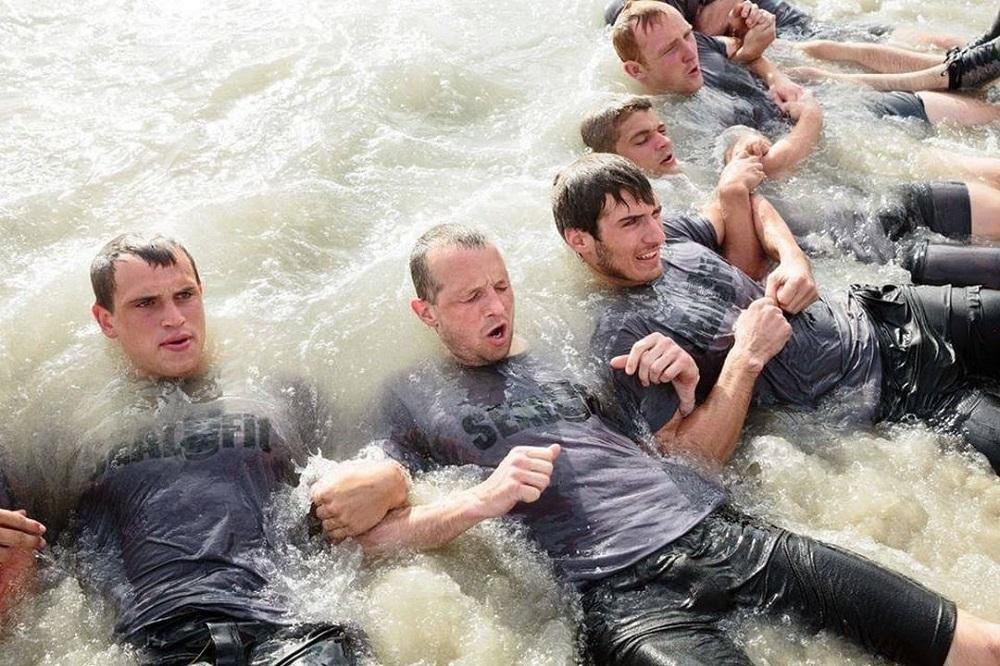 homens com braços entrelaçados no mar