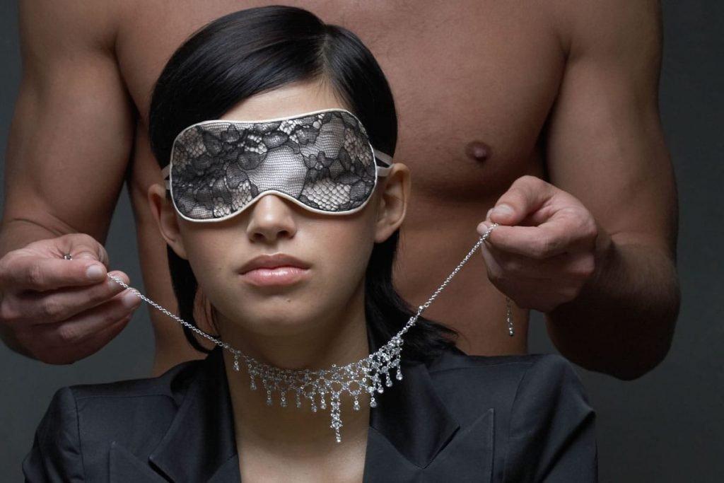 homem botando colar em mulher vendada